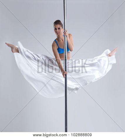 Flexible girl doing gymnastic split on pylon