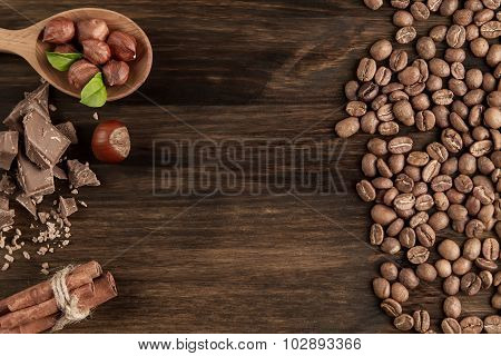Chocolate Bar, Shelled Hazelnuts, Roasted Coffee Beans, Cinnamon On Wooden Background, Close Up