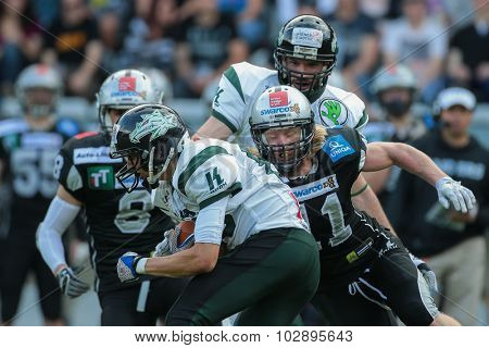 INNSBRUCK, AUSTRIA - JULY 12, 2014: DB Enrico Martini (#11 Raiders) tackles the ball carrier during an Austrian football league game.