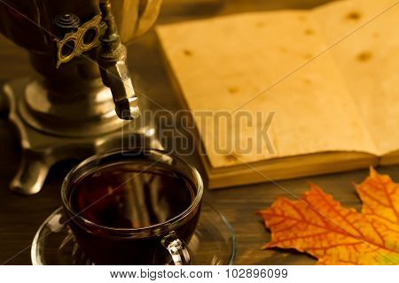 Tea Still Life With Samovar, Maple Leaves, On Wooden Background. Empty Open An Old Vintage Book. Rus