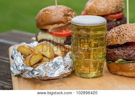 Tasty grilled burger, fried potato and glass of beer.