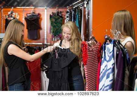 Cheerful Teenage Girls Trying Dresses