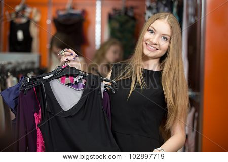 Attractive Woman Carrying Bunch Of Garments In Shop