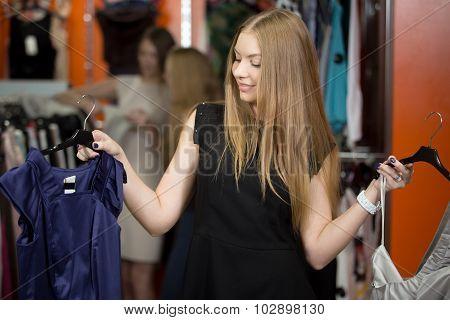 Smiling Woman Choosing Between Two Garments In Shop