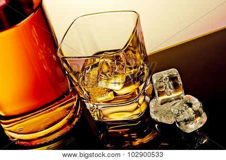 Top Of View Of Glass Of Whiskey Near Bottle And Ice Cubes On Table With Reflection