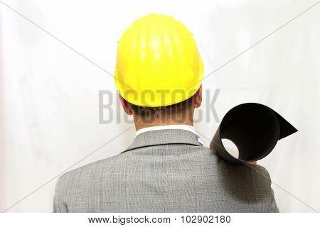 Portrait of worker in helmet holding a plan
