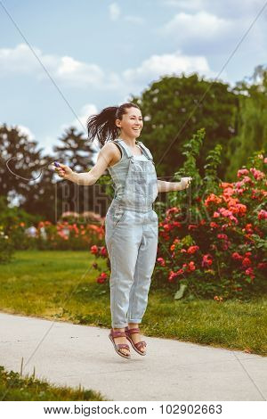 Sport and activity lifestyle concept. Cute woman jumping with skipping rope