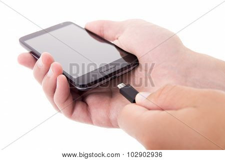 Smart Phone With Blank Screen And Charger In Male Hands Isolated On White