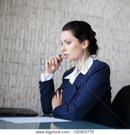 Young Brunette Businesswoman Thinking In Office