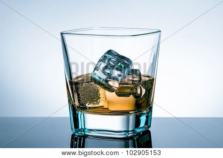 Glass Of Whiskey With Ice Cubes On Bar Table With Reflection On Light Blue Tint Background
