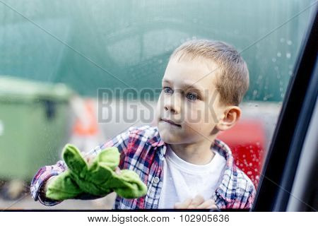 boy diligently washes a window in the car