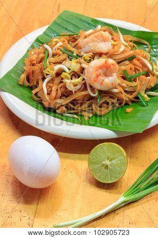 Selective Focus Thai Noodle Or Padthai With  Shrimp And Blur Vegetable,lemon,eggs On Wood  Backgroun
