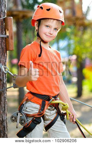 Cute boy shows thumb up with climbing equipment in an adventure park