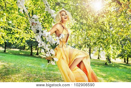 Attractive blonde beauty on a flower swing in a park