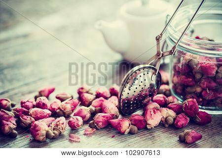 Rose Buds Tea, Tea Strainer Closeup, Glass Jar And Teapot On Background. Selective Focus.