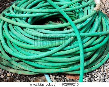 Green Water Hose On The Rock background.