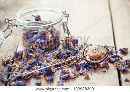 Healthy Forget Me Not Tea In Glass Jar And Strainer On Kitchen Table. Selective Focus.