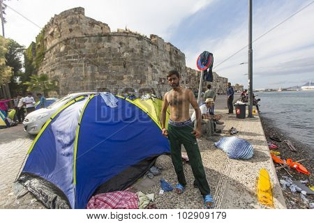 KOS, GREECE - SEP 27, 2015: Unidentified war refugee near the tents. Kos island is located just 4 kilometers from the Turkish coast, and many refugees come from Turkey in an inflatable boats.