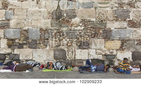 KOS, GREECE - SEP 27, 2015: War refugee sleeping on the ground along stone wall. Kos island is located just 4 kilometers from Turkish coast, and many refugees come from Turkey in an inflatable boats.