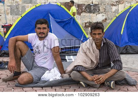 KOS, GREECE - SEP 27, 2015: Unidentified war refugees near tents. More than half are migrants from Syria, but there are refugees from other countries -Afghanistan, Pakistan, Iraq, Iran, Mali, Eritrea.