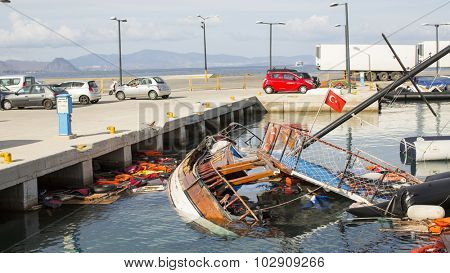 KOS, GREECE - SEP 27, 2015: Life Jackets discarded and sunken Turkish boat in the port. Kos island is located just 4 kilometers from the Turkish coast, and many refugees come from Turkey  in an boats.