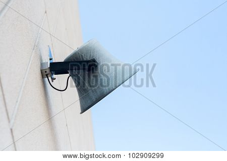Grey speaker on the wall against a blue cloudless sky
