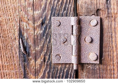 Old rusty hinge with bolts in it over a wooden background