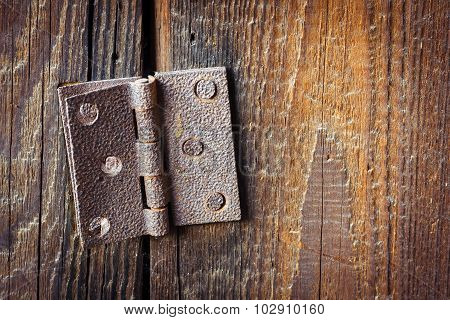 Old broken rusty hinge with bolts in it over a wooden background