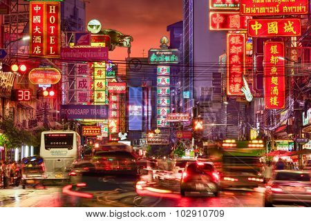 BANGKOK, THAILAND - SEPTEMBER 27, 2015: Traffic on Yaowarat Road passes below lit signs in the Chinatown district at dusk.
