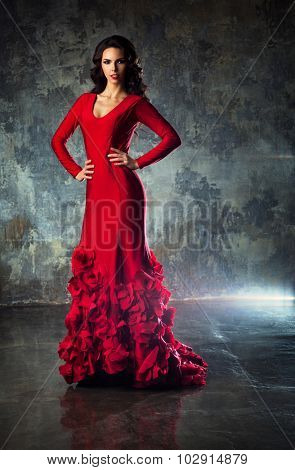 Young slim sexy fashion woman in long red dress standing on stone wall background.
