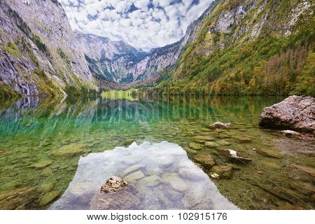 Fabulously beautiful lake Koenigssee in Austria. Mountainous lakeside reflected in the smooth water of the lake, like the wings of butterfly