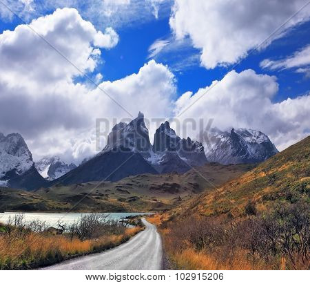 Patagonia. Vertiginous landscape in the Chilean Andes. The road between turned yellow hills goes to snow-covered black rocks of Los Kuernos.