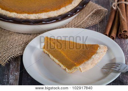 Slice Of A Pumpkin Pie On Rustic Table
