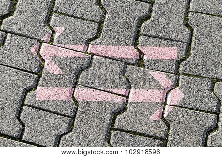 Arrows On Grey Tiles Of The Foot Path