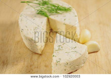 Cottage cheese parsley, garlic on a cutting board.