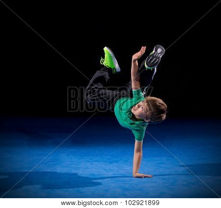 Little boy breakdancer on black