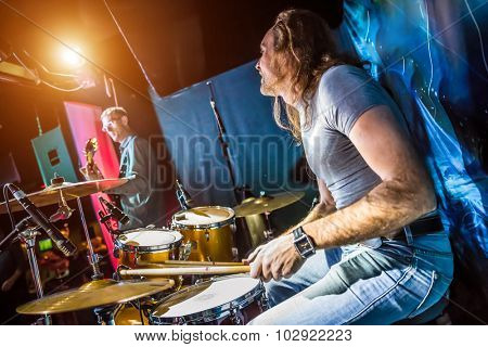 Drummer playing on drum set on stage. Warning - authentic shooting with high iso in challenging lighting conditions. A little bit grain and blurred motion effects.