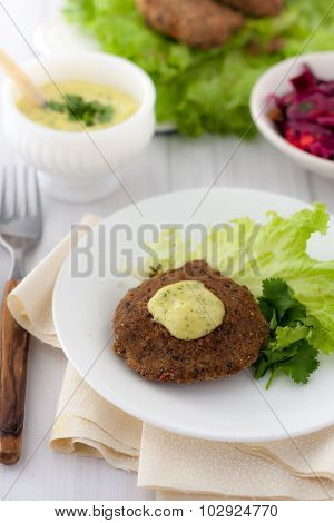 bean burger without a bun served on a plate with aioli sauce