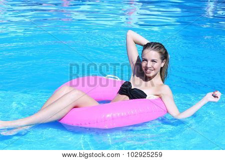 Young woman resting on pink rubber ring in swimming pool