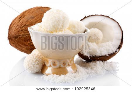 Candies in coconut flakes and fresh coconut isolated on white