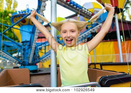 Cute little happy smiling girl riding a Carnival Carousel at summer theme park