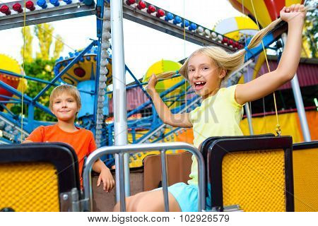 Cute little happy smiling kids riding a Carnival Carousel at summer theme park
