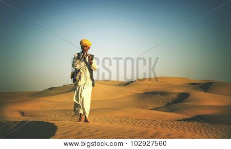 Indigenous Indian Man Playing Wind Pipe In A Desert Concept