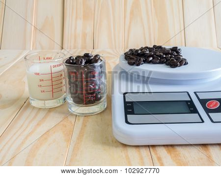 Coffee beans, measuring cup of fresh milk and dIgital balance Scale on wooden board