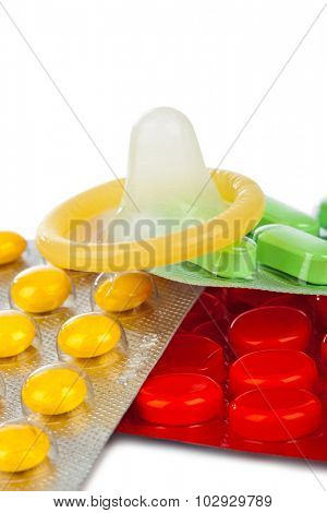 Condom and pills isolated on white background