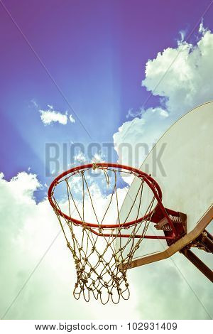 Old Basketball Board And Hoop On Blue Sky With Clouds Background