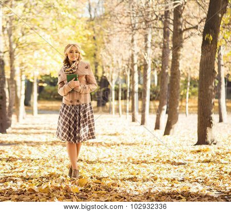 Beautiful woman being alone in the autumn park with a book.