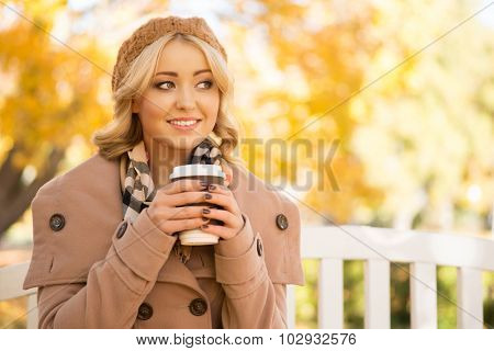 Beautiful young woman enjoying coffee smell in the park in autumn.