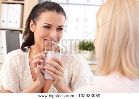 Close up of happy casual brunette receptionist with coffee cup in hand at business office, smiling.