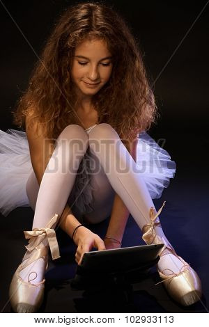 Pretty ballet student using tablet computer while resting.